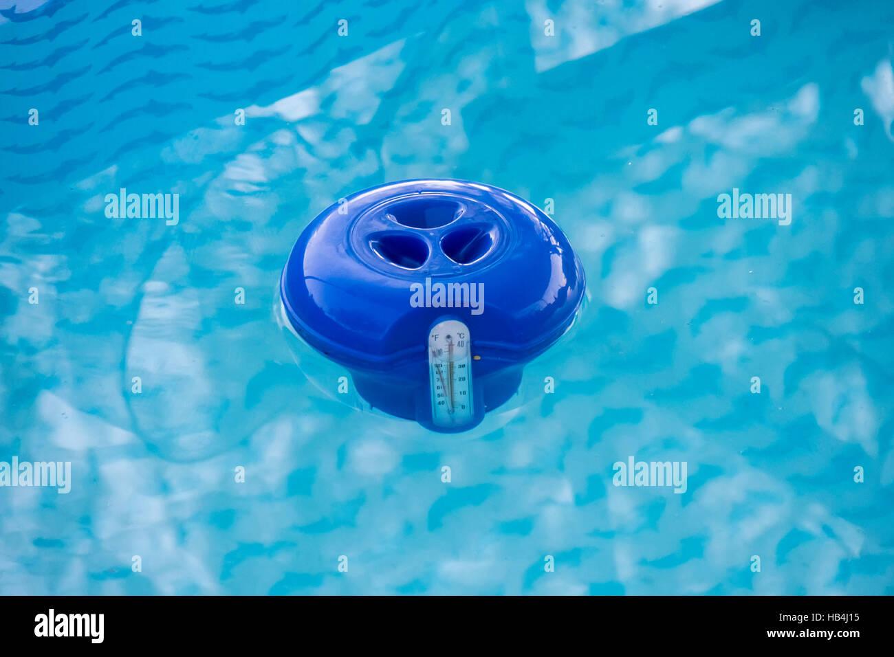 Piscina azul dispensador de cloro en el agua Foto de stock