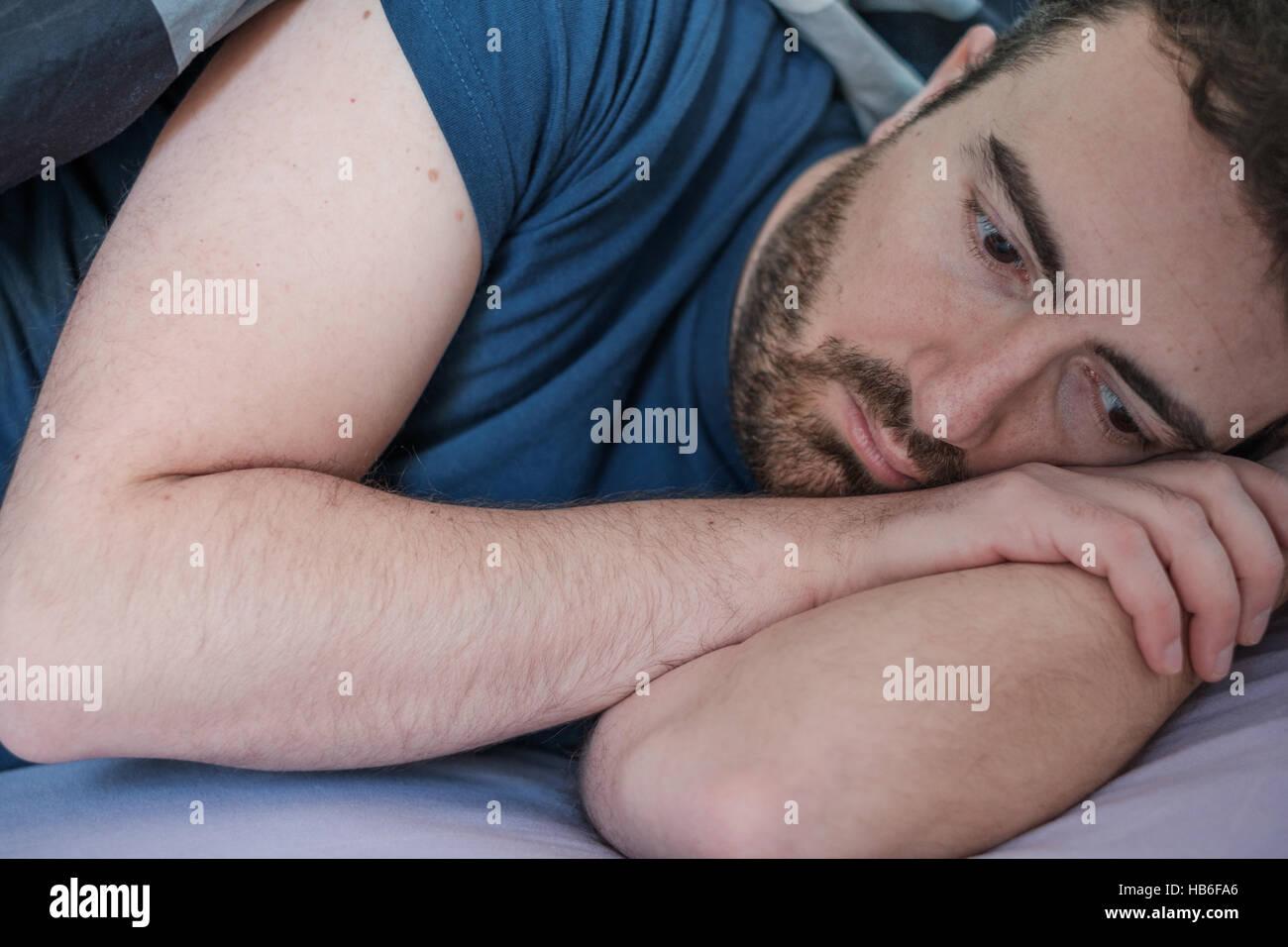 Pisado el hombre yace en su lecho sintiéndote mal Imagen De Stock