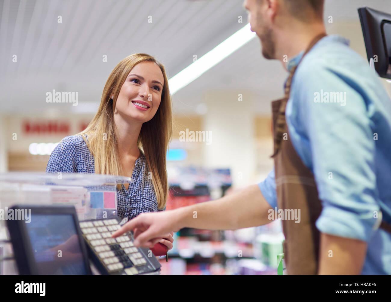 La mujer junto a la caja registradora hablando con la vendedora Foto de stock