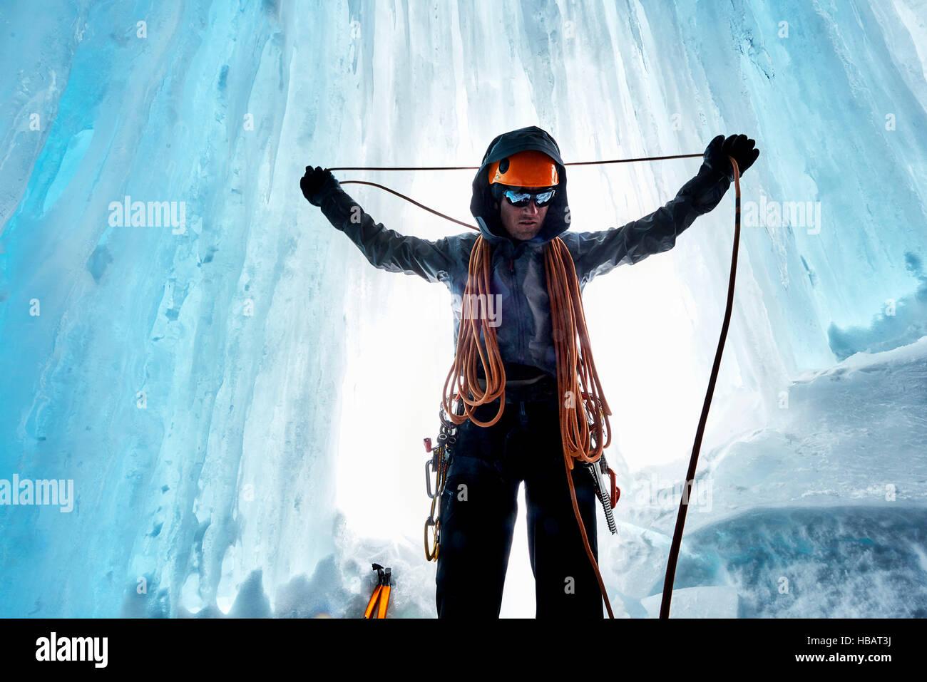 El hombre en la cueva de hielo preparando la cuerda de escalada, Saas Fee, Suiza Imagen De Stock