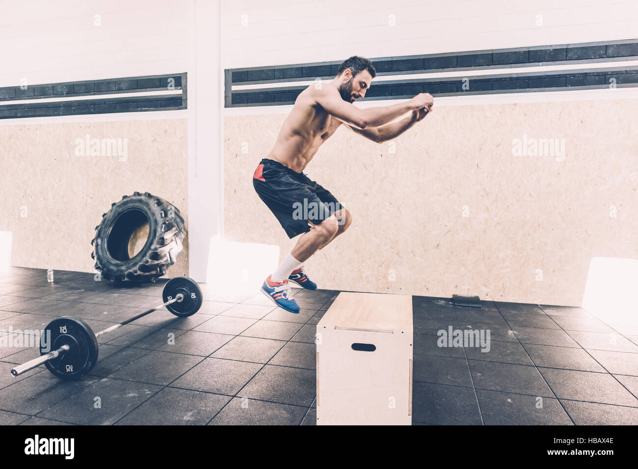 Joven saltando sobre verificación en cross training gimnasio Imagen De Stock