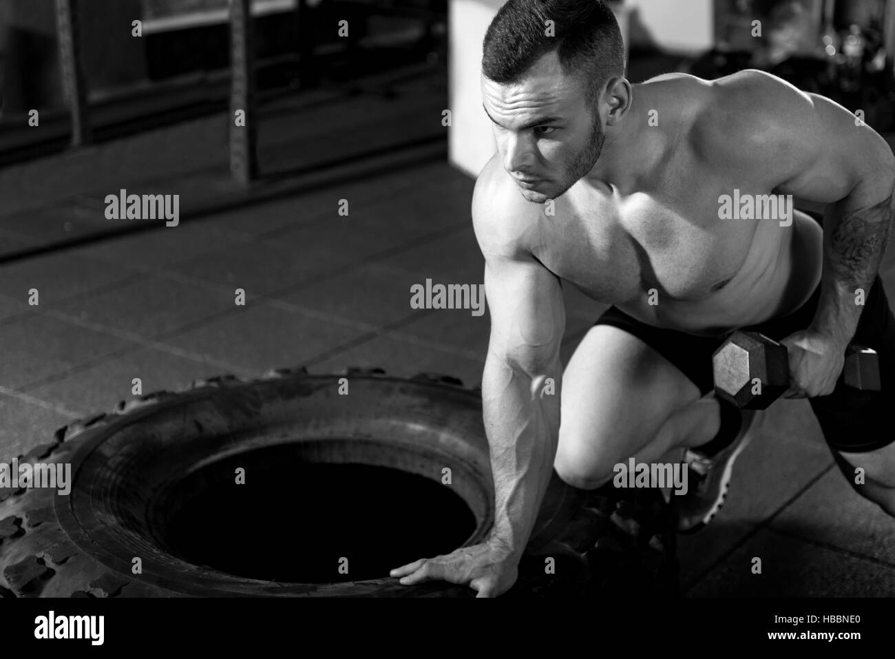 Atlético hombre con pesas entrenamiento muscular Imagen De Stock
