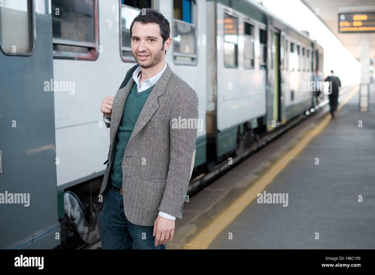 Hombre de pie esperando el tren en una estación de tren plataforma Foto de stock