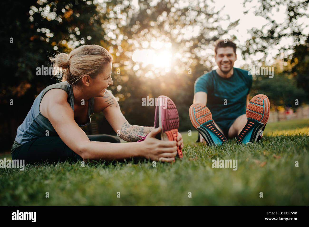 Ejercicios de estiramiento pareja afuera en el parque. Joven Hombre y mujer ejercen juntos en la mañana. Imagen De Stock