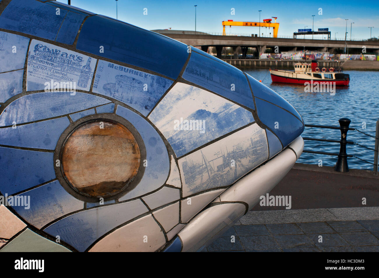 La escultura Big Fish por John amabilidad, Donegall Quay, Río Lagan, Belfast, Irlanda del Norte, Reino Unido. Atrás, el barco turístico casco rojo Mona amarrados en T Foto de stock