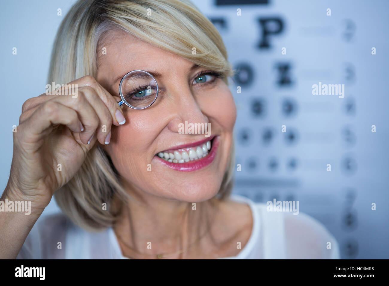 Paciente femenina mirando a través de una lupa Foto de stock