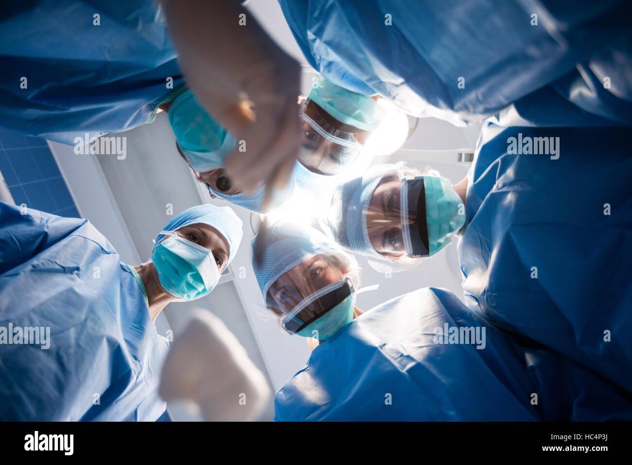 Grupo de cirujanos mirando a la cámara en la sala de operación Imagen De Stock