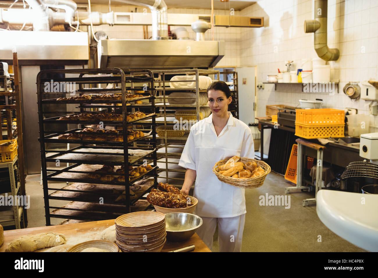 Baker femenino celebración cesta de alimentos dulces Foto de stock