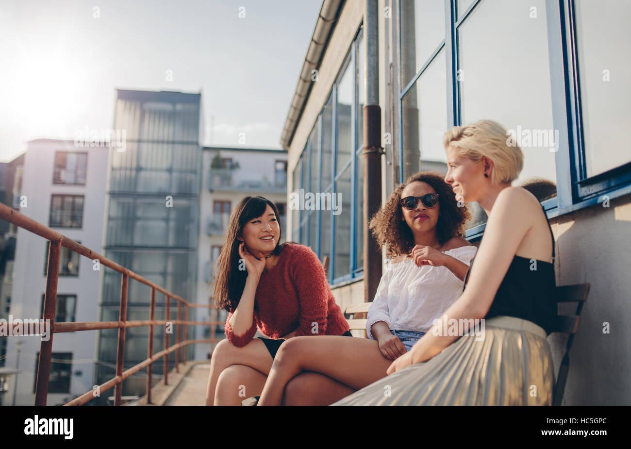Tres amigas jóvenes sentados en el balcón. Las mujeres relajarse al aire libre y conversando. Imagen De Stock