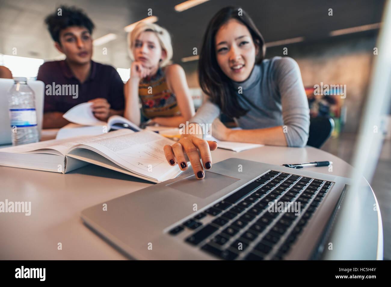 Estudiantes universitarios con laptop en una biblioteca. Un hombre y una mujer jóvenes estudian juntos. Imagen De Stock