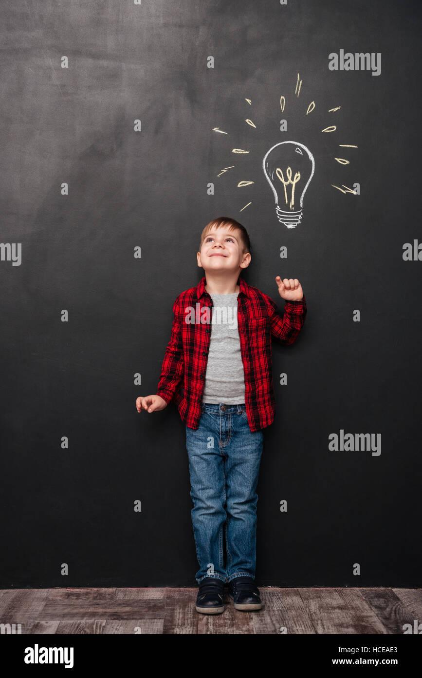 Imagen de poco chico lindo tener una idea sobre la pizarra con dibujos de fondo. Mirando a los dibujos. Foto de stock