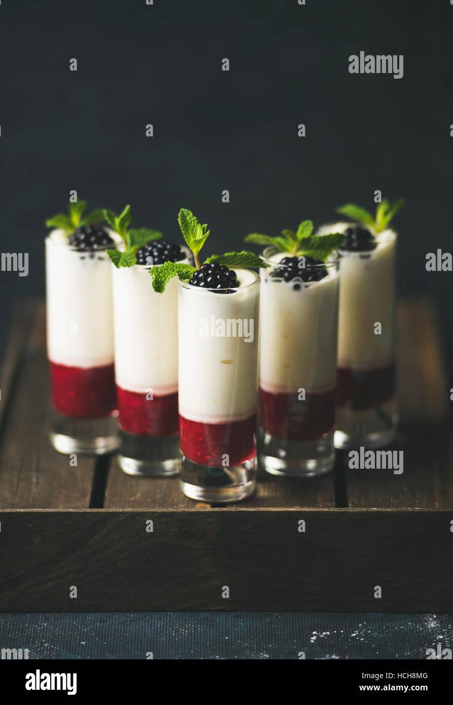 Postres caseros con blackberry y hojas de menta fresca en vidrios sobre la mesa de madera sobre fondo oscuro, el Imagen De Stock