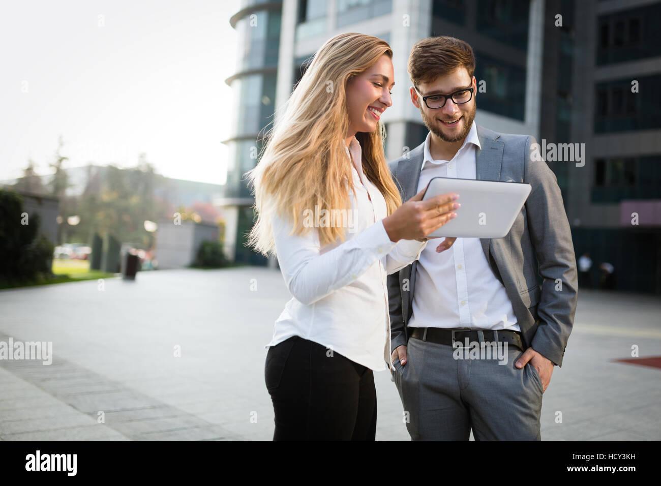Compañeros de trabajo hablando en exteriores y con tablet Imagen De Stock