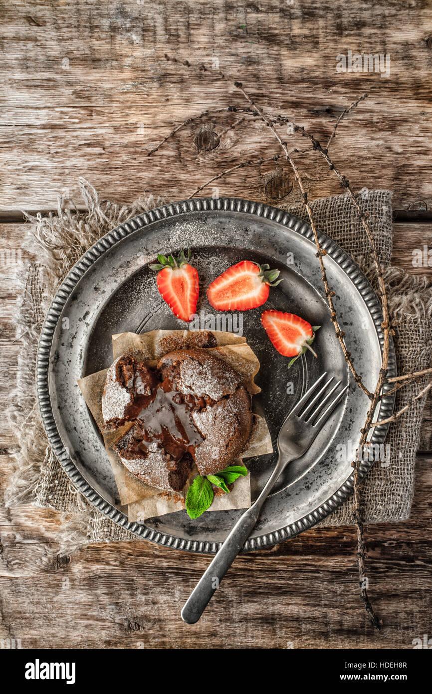 Fondant de chocolate con fresa y menta sobre la mesa de madera vertical Imagen De Stock