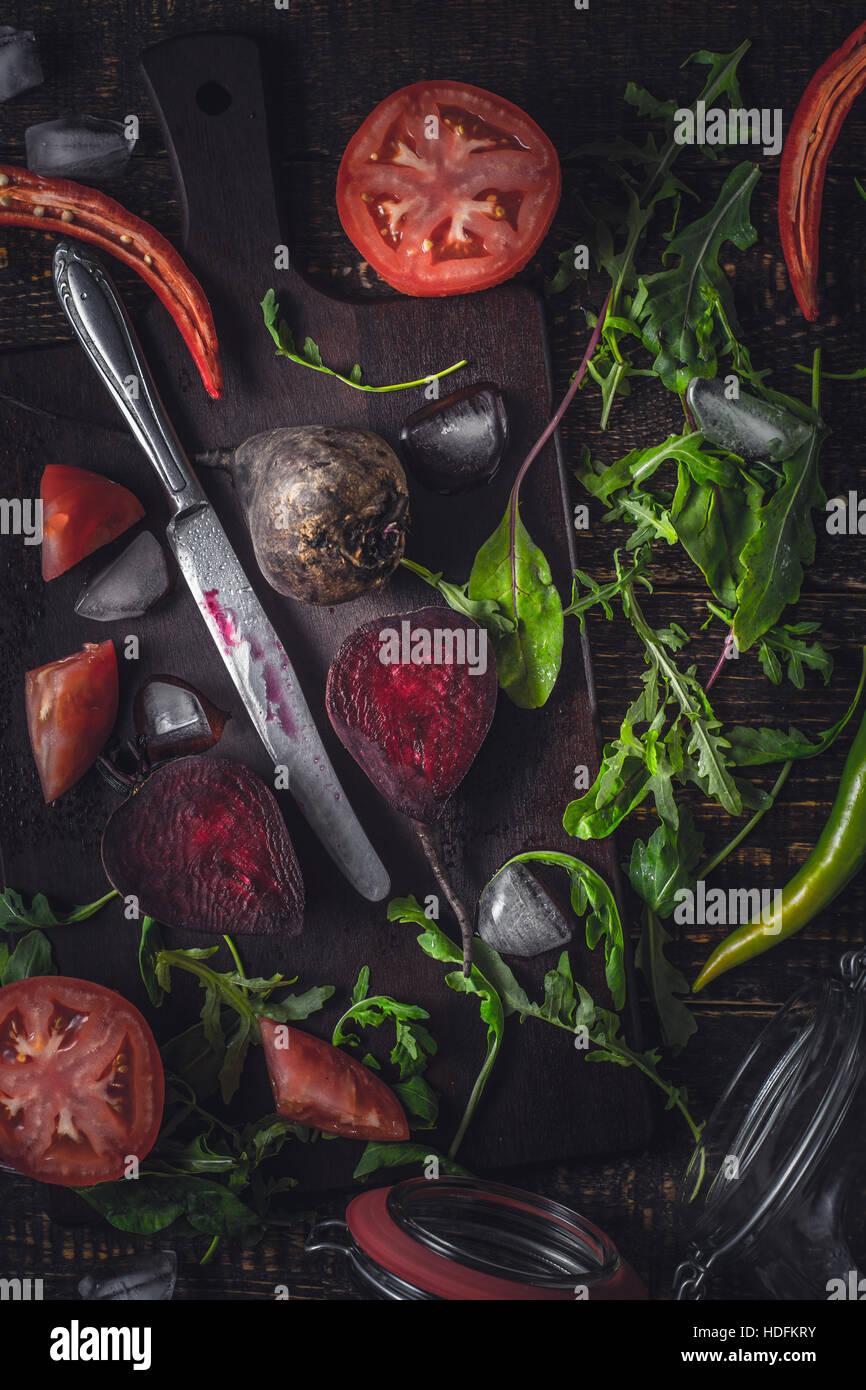 Ingredientes para el batido de vegetales sobre la mesa de madera antigua vertical Foto de stock