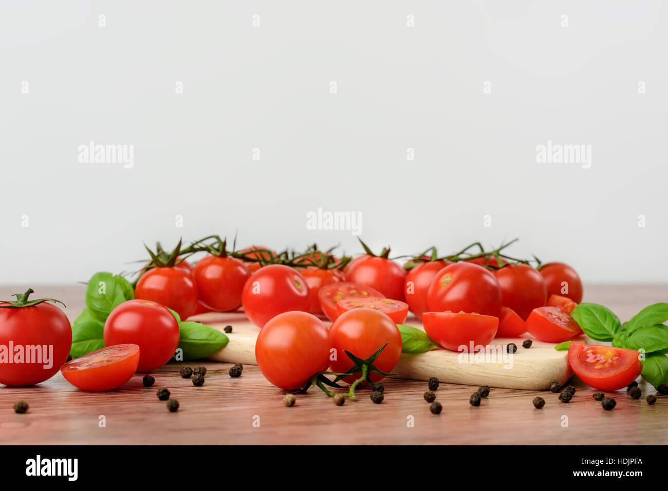 Mini tomaotes sobre la mesa de madera con fondo brillante. Imagen De Stock