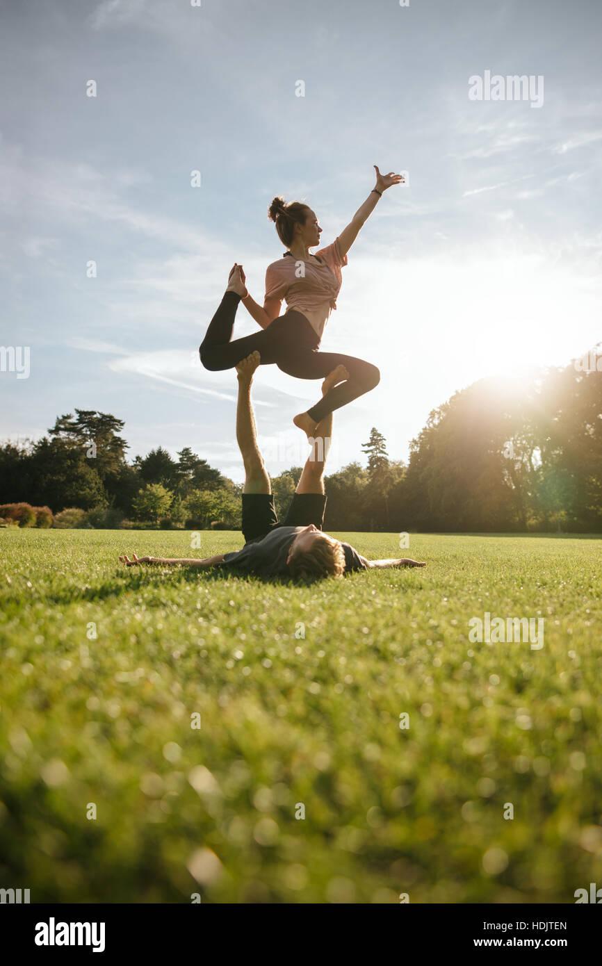 Disparo vertical de sana pareja joven haciendo yoga acrobático sobre el césped. Hombre y mujer el ejercicio Imagen De Stock