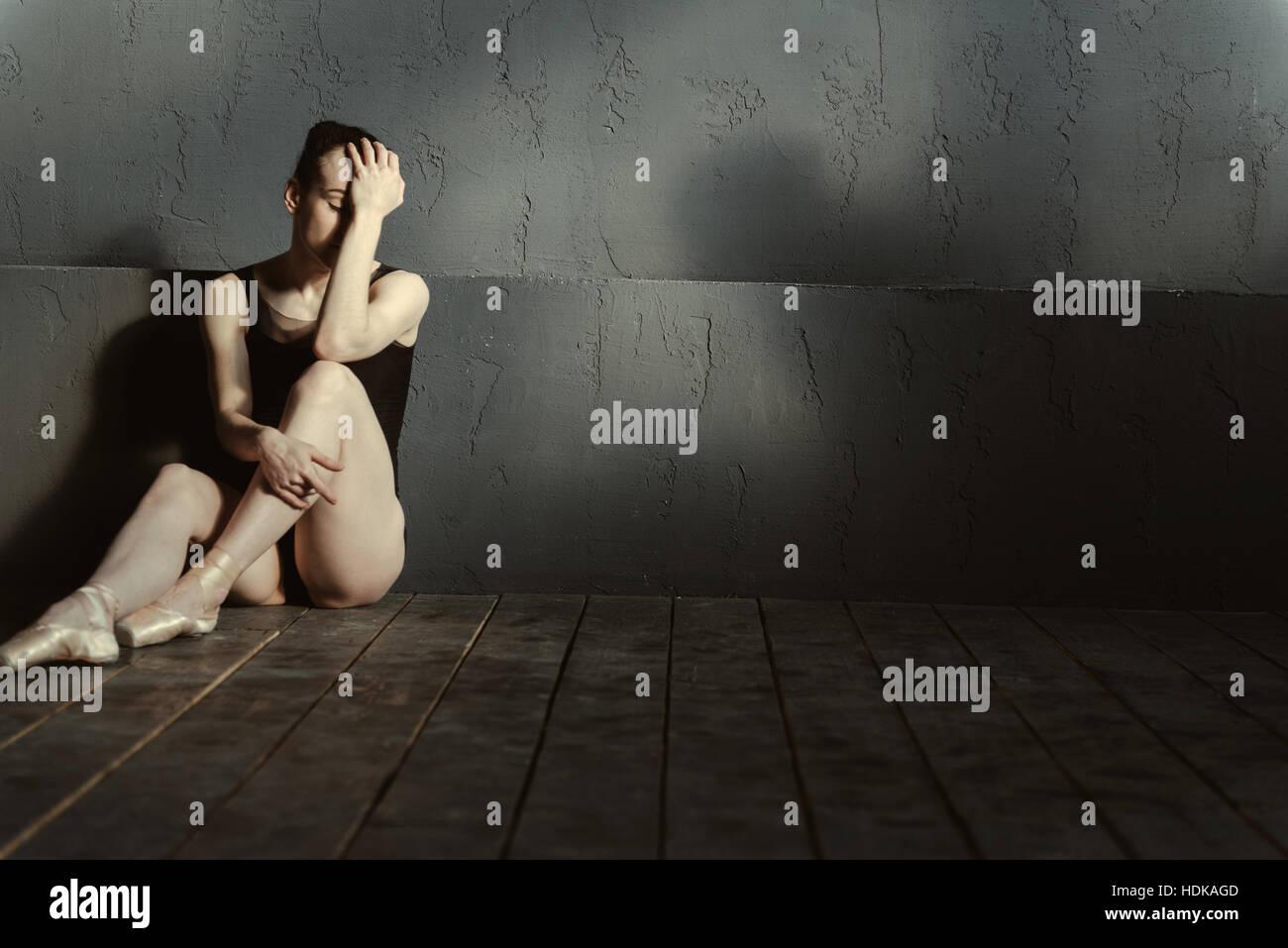 Decepcionado bailarina de ballet sentada en la oscuridad de la habitación iluminada Imagen De Stock