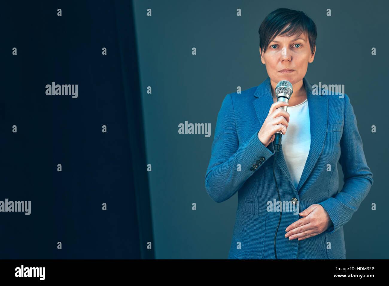 Periodista de la televisión femenina elegante reportaje doing business, sosteniendo el micrófono en la Imagen De Stock