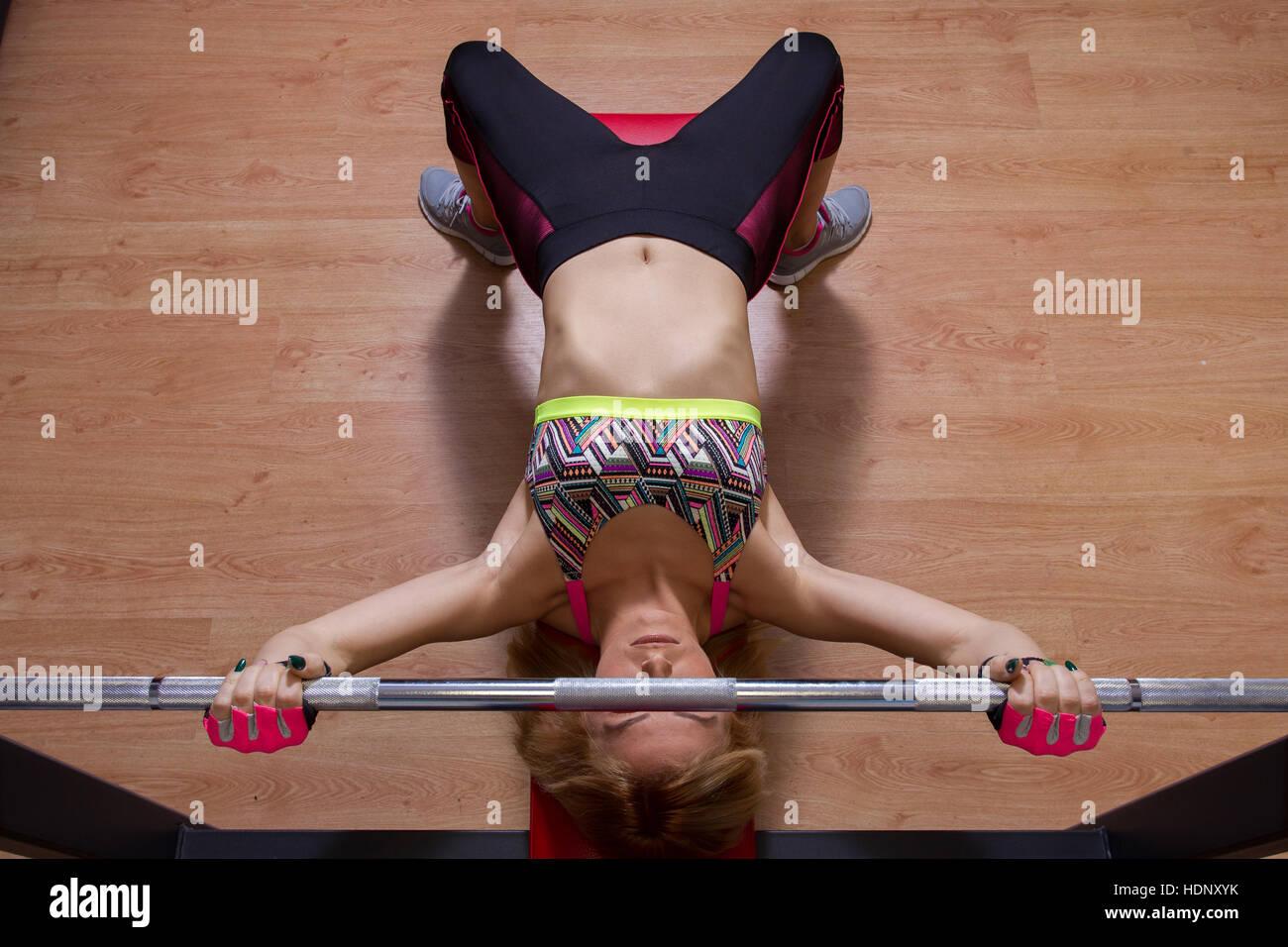 Ejercítese en el gimnasio de deportes, chica rubia entrenamiento en el gimnasio Imagen De Stock