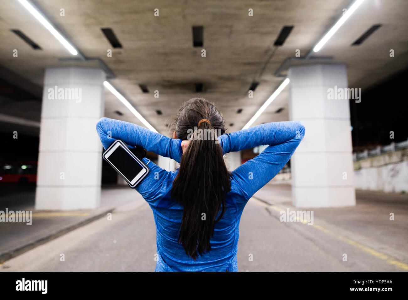 Joven corredora bajo el puente en la noche, descansando Foto de stock