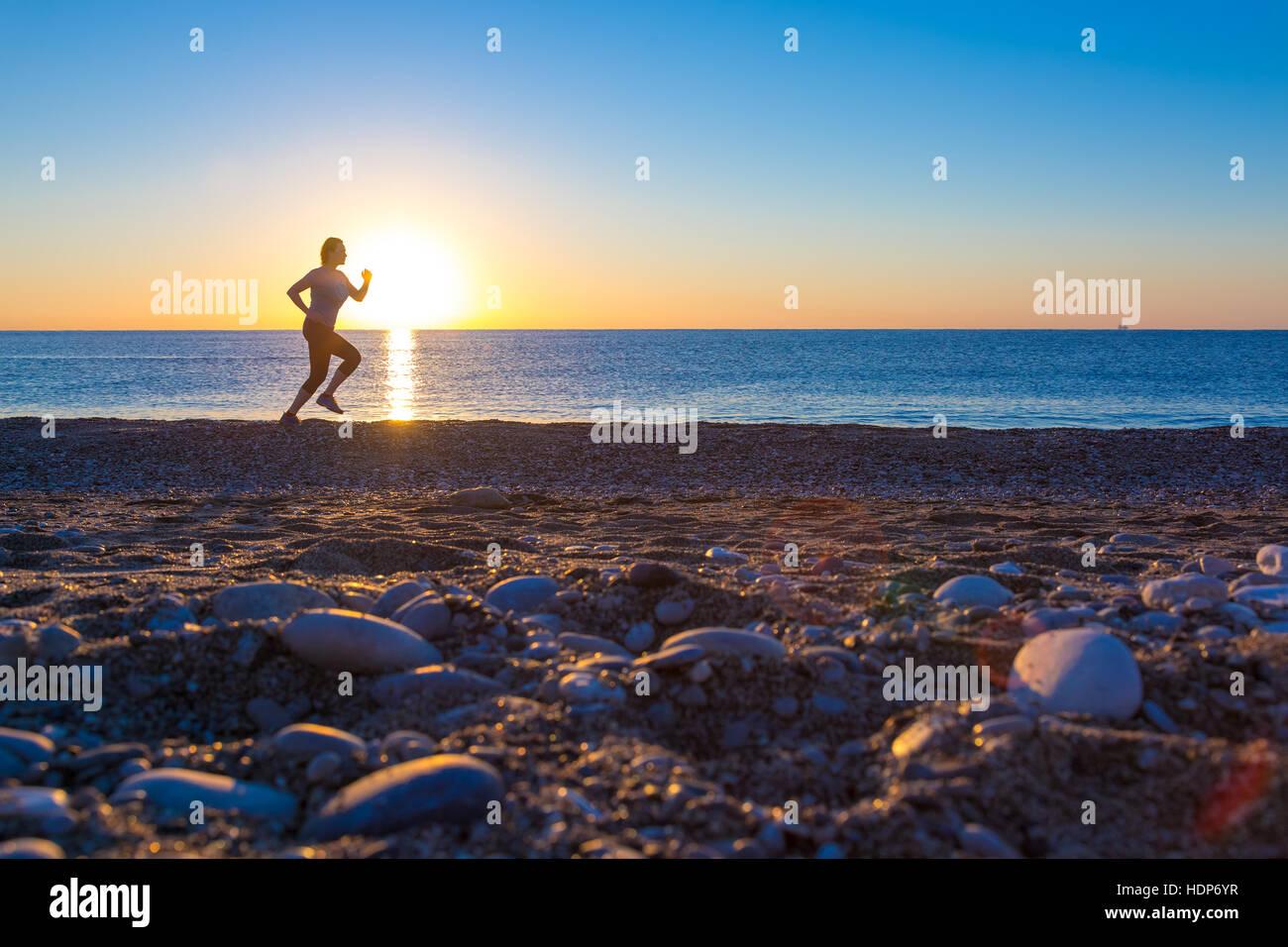 Silueta de Sportswoman en la playa al amanecer. Imagen De Stock