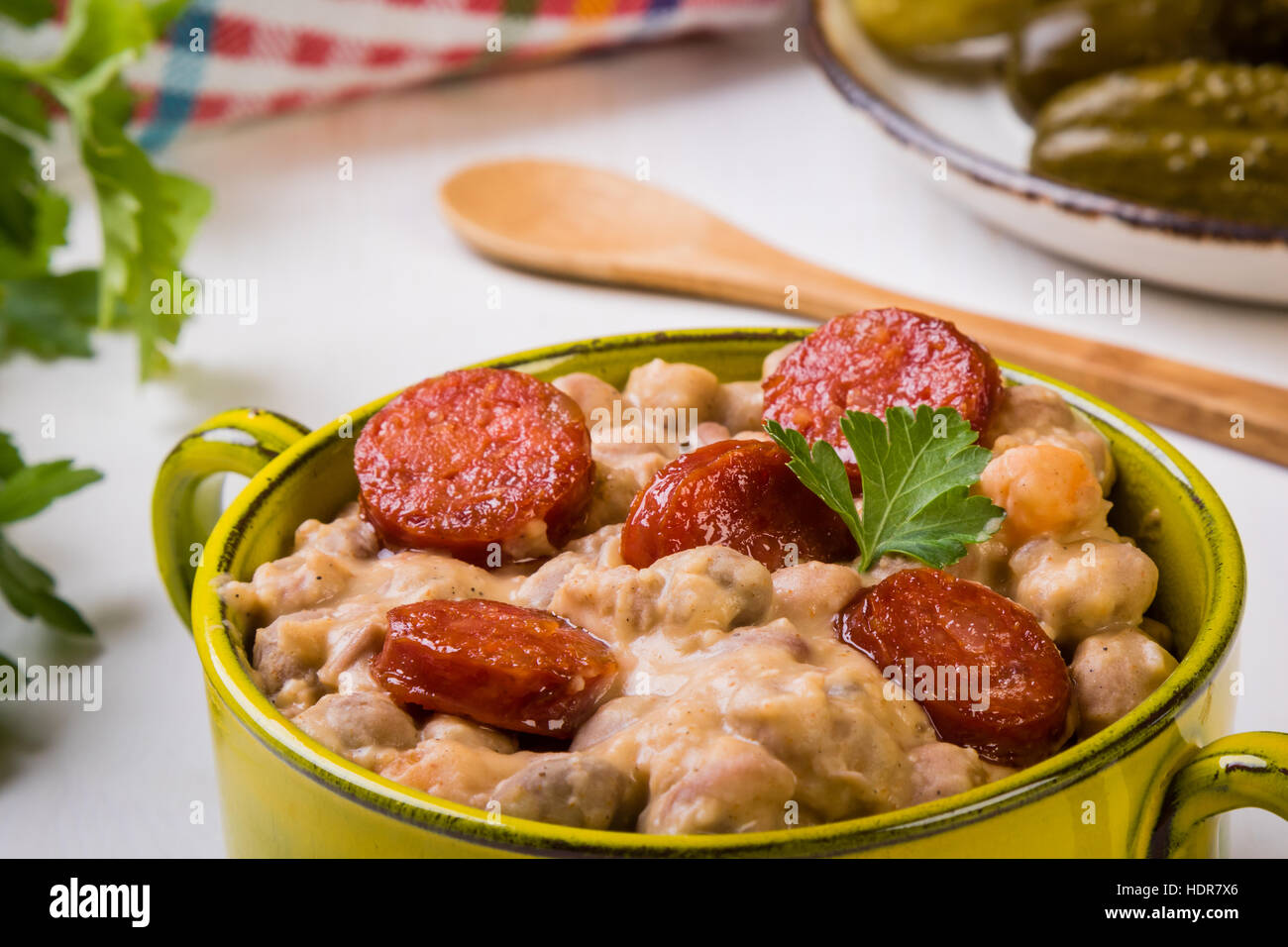 Un guiso de alubias con salchichas en tazón verde Imagen De Stock