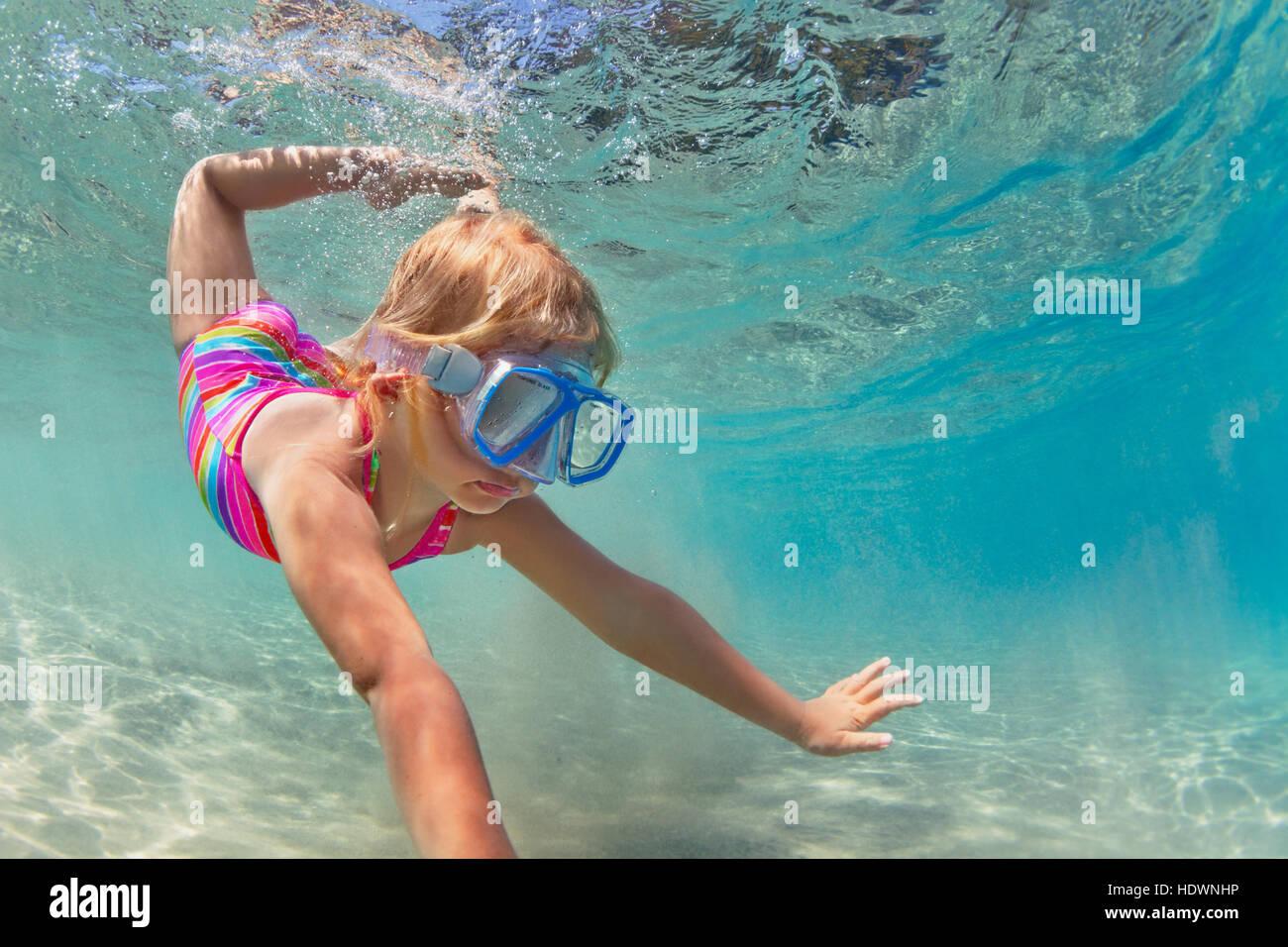 Feliz niña gafas de bucear, nadar y bucear bajo el agua con la diversión en el mar piscina estilo de vida Imagen De Stock