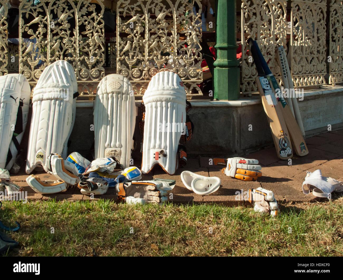 Guantes de cricket bat y almohadillas inclinándose hacia arriba contra la verja de hierro decorativo en la luz de la tarde Foto de stock