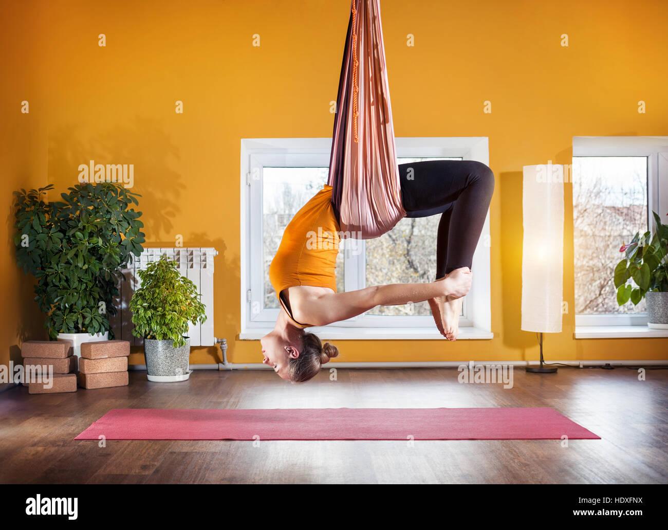 Mujer joven haciendo antigravity yoga posición de flexión hacia atrás en el studio con paredes amarillas Imagen De Stock