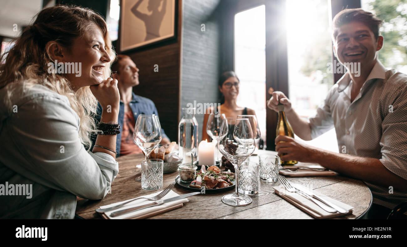 Grupo de amigos disfrutando de una cena con vino en un restaurante. Hombre y mujer joven feliz cenando en un restaurante. Imagen De Stock