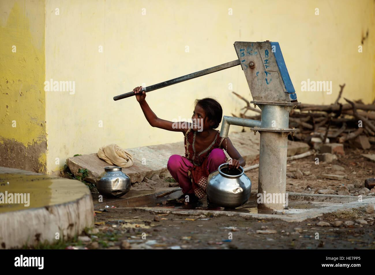 Indian Village chica sonriente y tubería de agua borewell Imagen De Stock