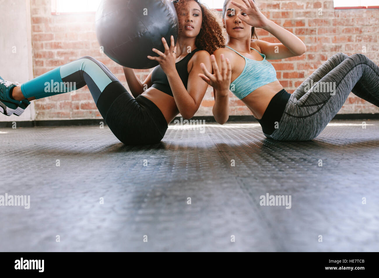 Dos mujeres jóvenes a ejercitarse con balón medicinal en el gimnasio. Las niñas que trabajan en el Imagen De Stock