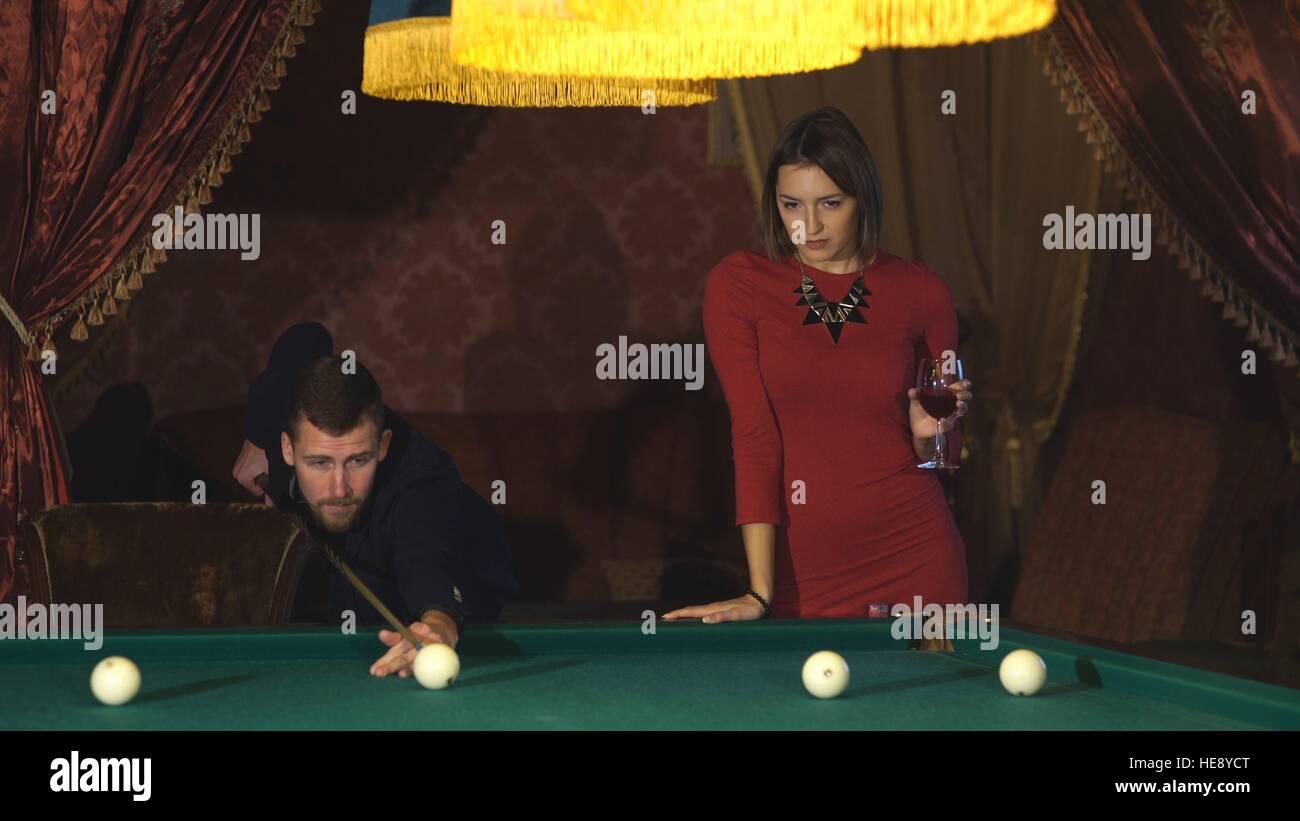 Chica de vestido rojo jugando billar