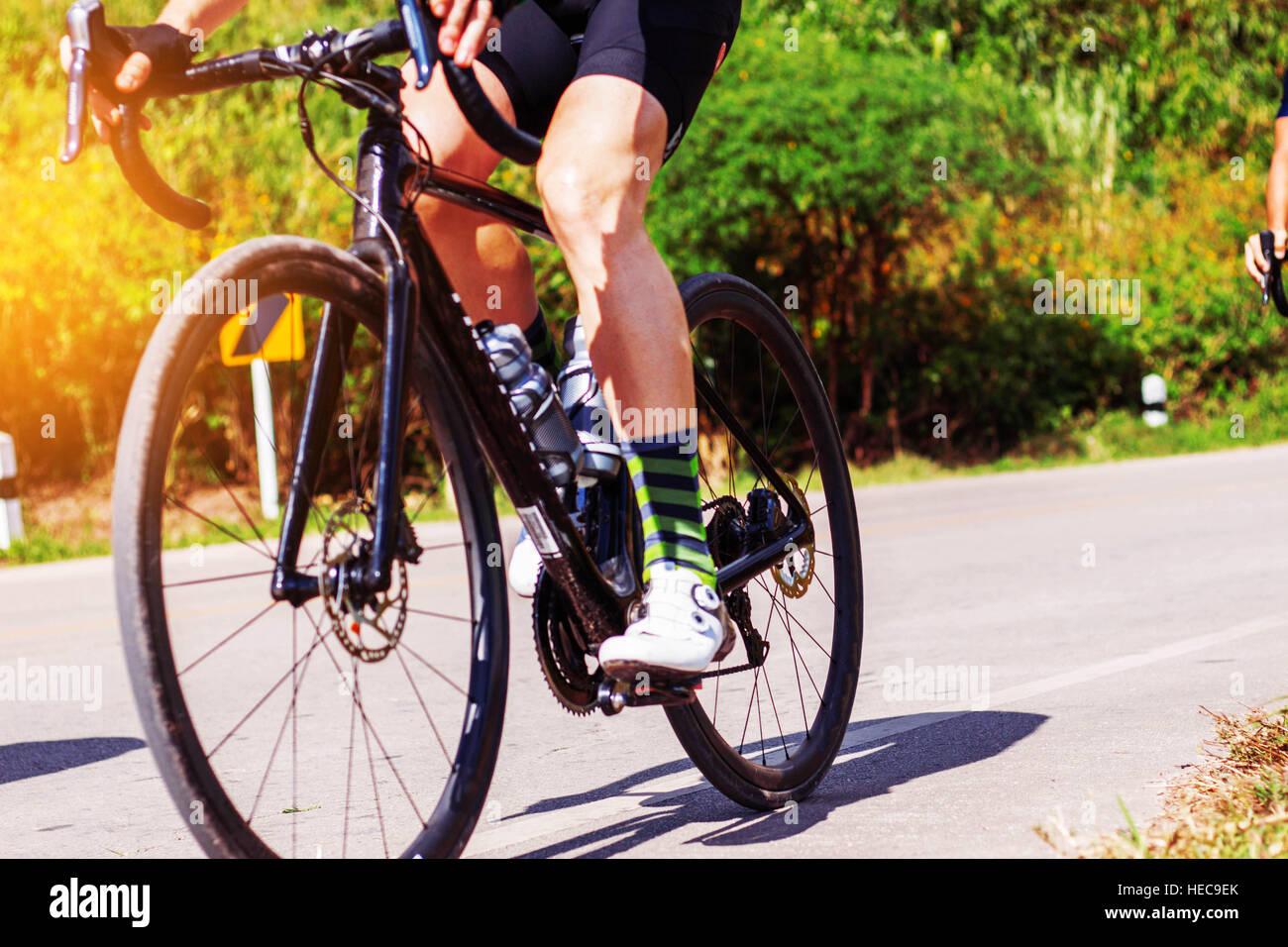 Joven iba en bicicleta por la carretera en la mañana. Imagen De Stock