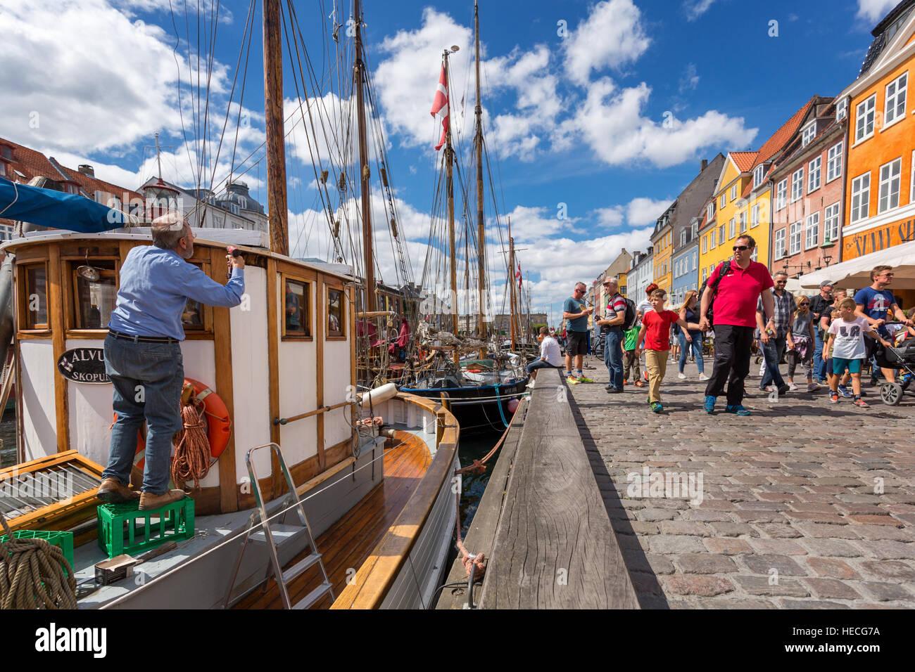 Un hombre pintando sus embarcaciones a lo largo de canal de Nyhavn, Copenhague, Dinamarca Foto de stock