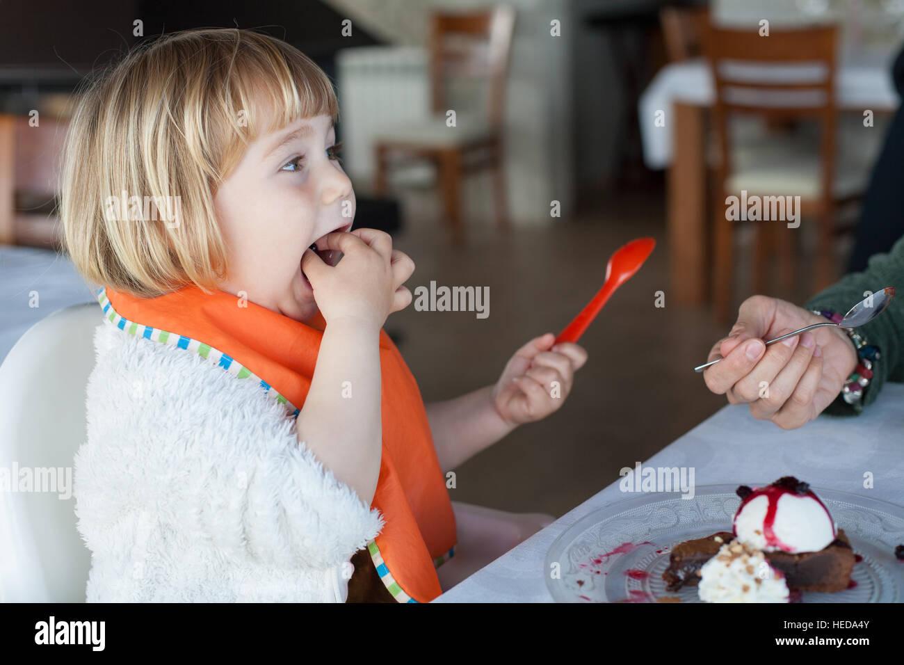 Niño de dos años con una cuchara de plástico naranja de comer con las manos en la boca compartir Imagen De Stock