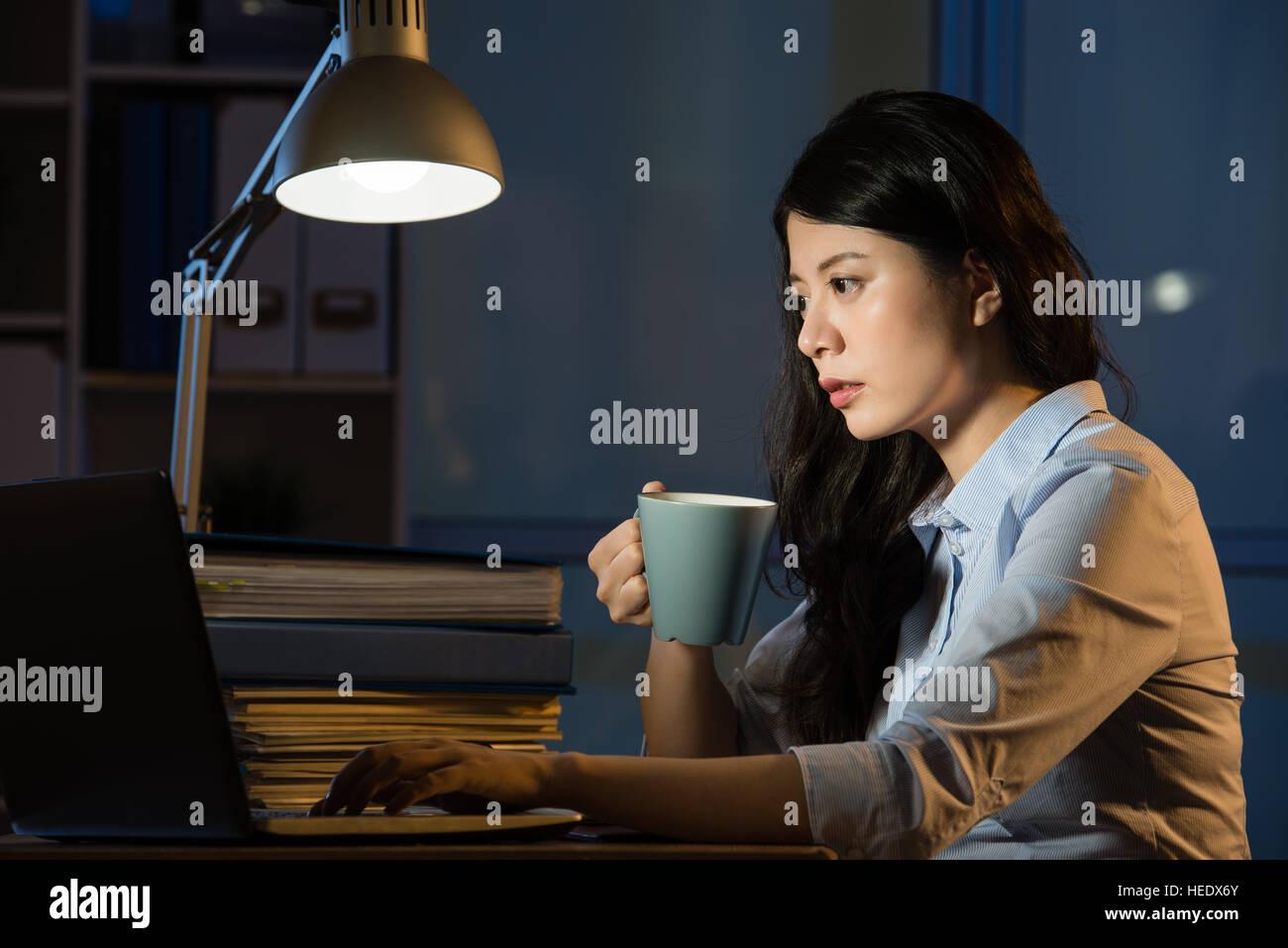 Mujer de negocios asiáticos beben café refrescante trabajando horas extraordinarias nocturnas interiores oficina de fondo. Foto de stock