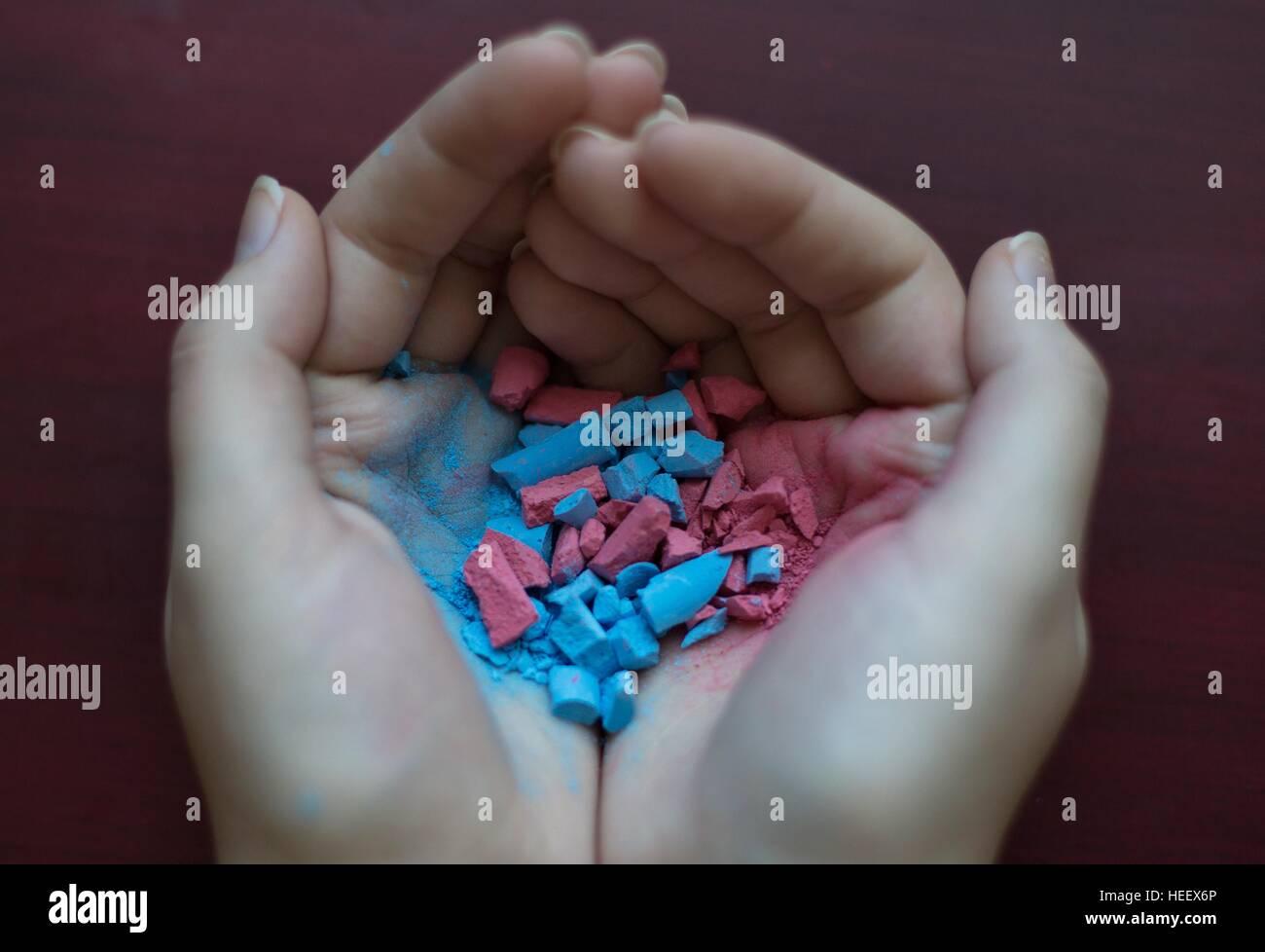 Ahuecada manos sosteniendo ambos rosa y azul chalk, mezclado y desintegraron juntos. Foto de stock