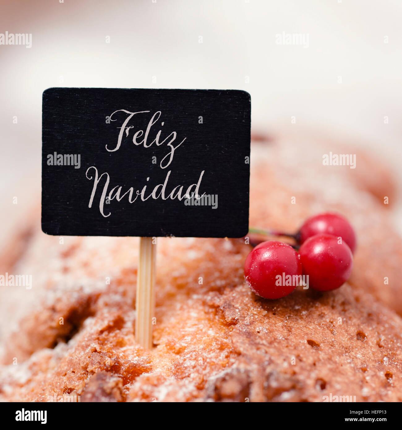 Primer plano de un cartel con el texto negro feliz navidad, feliz navidad en español, encabezando un pastel Imagen De Stock