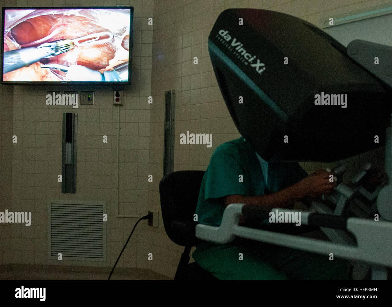 El Dr. Samuel Cancel-Rivera, un obstetra/ginecólogo médico mira a través de un sistema de imágenes en 3D el monitor de duplicación (superior izquierda) mientras opera a un paciente utilizando la última state-of-the-art Robotic Surgical System en el William Beaumont Army Medical Center, el 2 de mayo. El cirujano-manipulado sistema permite a los cirujanos operar con la articulación de instrumentos que se doblan y giran mucho mayor que la muñeca humana a través de una incisión más pequeña que un centímetro.William Beaumont Army Medical Center realizó la primera cirugía robótica en el Departamento de Defensa utilizando el sistema quirúrgico. En primer WBAMC DoD para utilizar robo Foto de stock