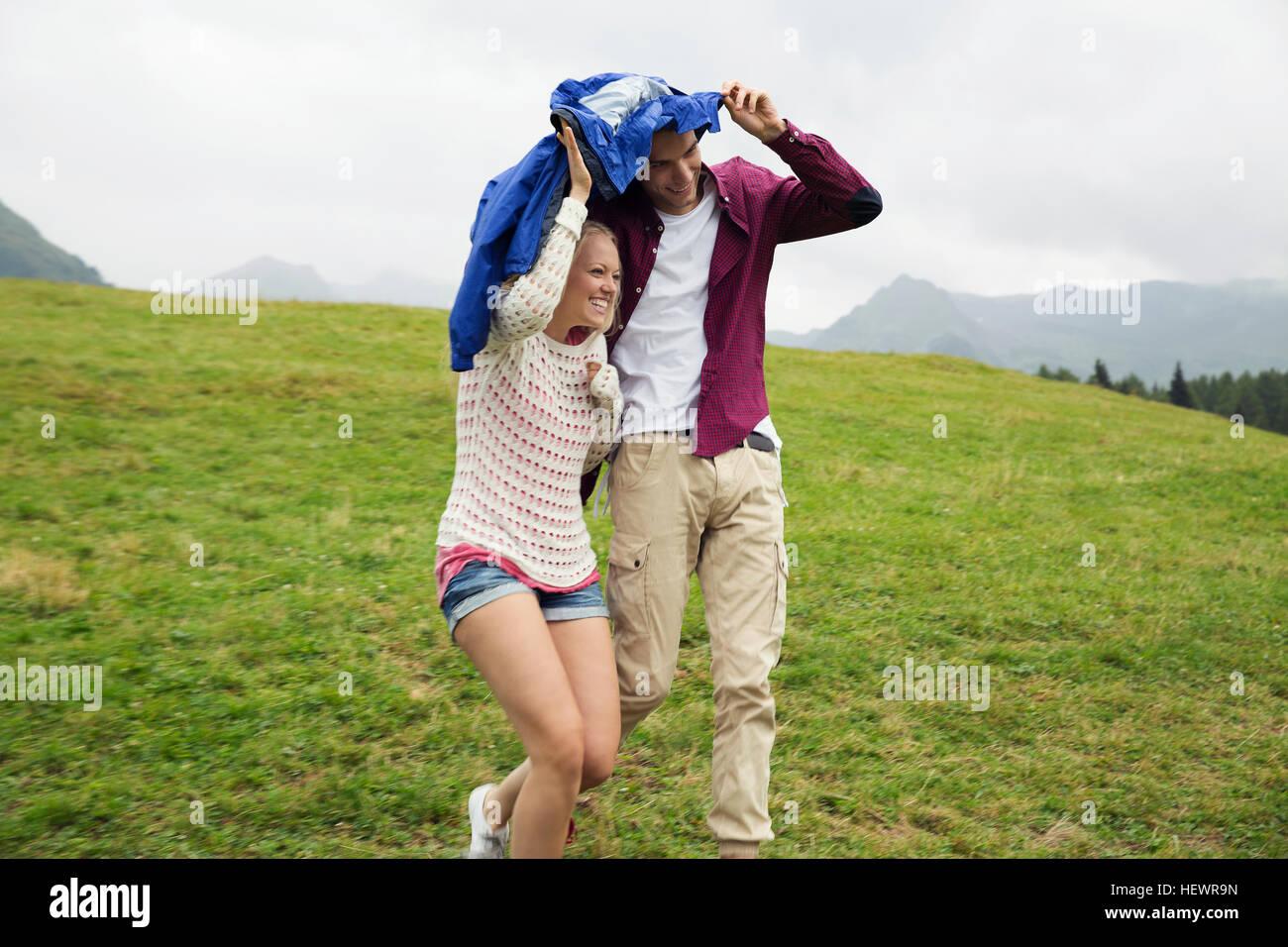 Pareja joven corriendo colina abajo sosteniendo rompevientos en lluvia, Sattelbergalm, Tirol, Austria Foto de stock