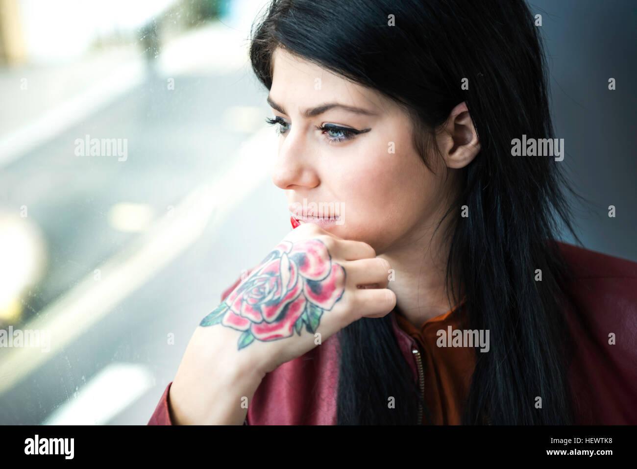 Mujer joven con tatuaje en la mano, mirando a través de la ventana Imagen De Stock