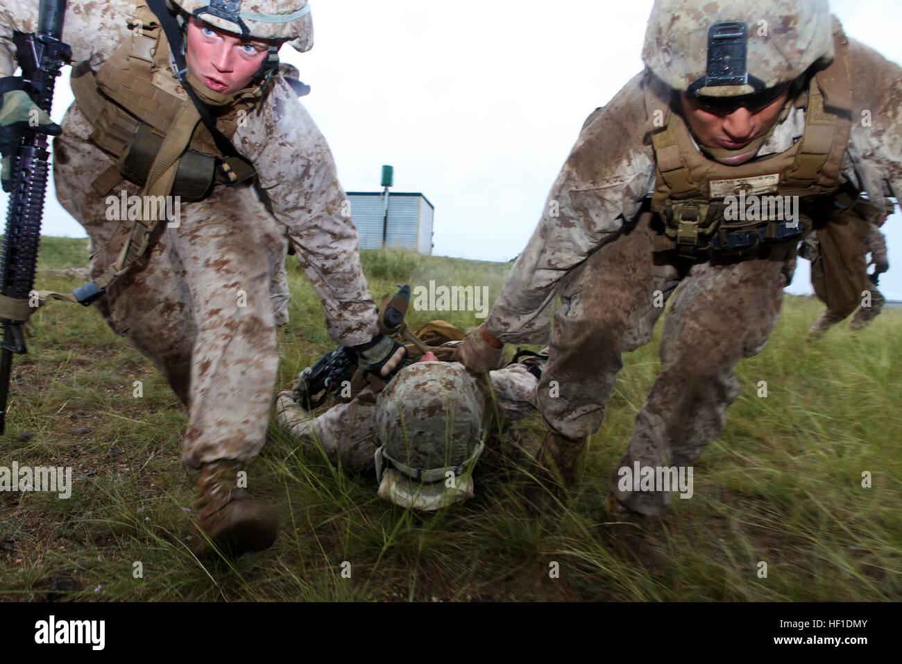 Lance Cabos Rob Magnuson y Rafael Cortez buddy arrastre Lance Cpl. Jeff Landis, un simulacro de accidente, mientras Foto de stock