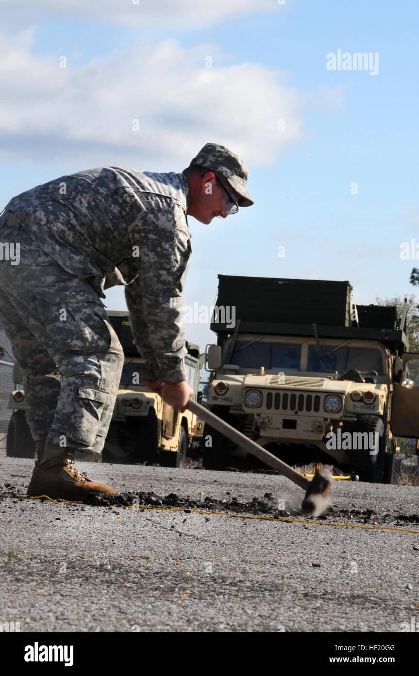 El Sgt. Chaven, la Guardia Nacional de Alabama, establece un cable guía ancla en asfalto durante su ejercicio Imagen De Stock
