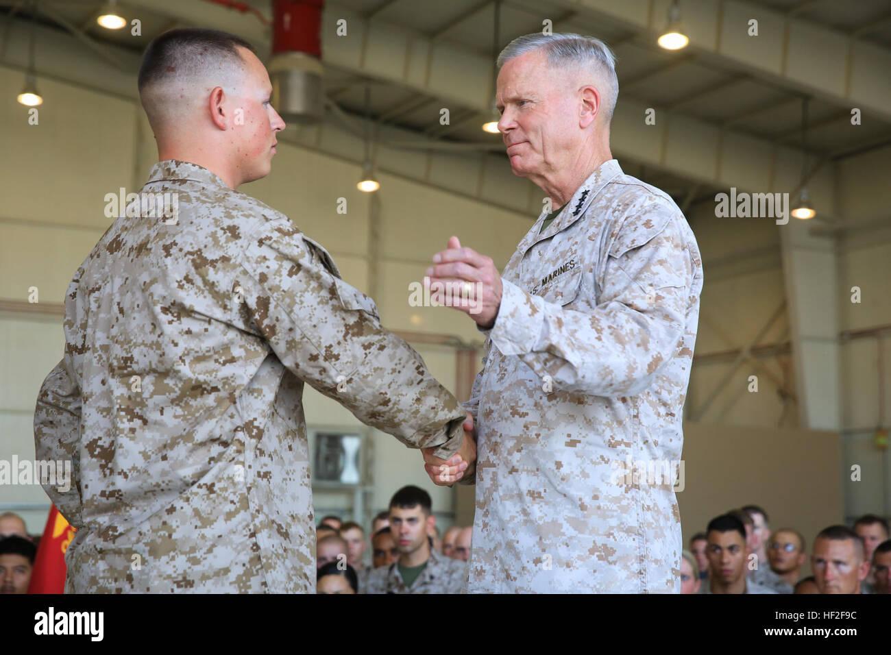 Cuerpo de Marines de EE.UU General James F. Amos, Comandante del Cuerpo de Infantería de Marina, felicita a Cpl. Mateo Padilla, un mecánico de fuselajes asignada al grupo de logística de la Aviación Marina 17 (MALS-17), el Grupo de aviones marinos - Afganistán (MAG-A), después de la promoción él meritoriamente durante una visita a las fuerzas desplegadas a bordo de Camp Bastion, provincia de Helmand, Afganistán, Septiembre 6, 2014. La visita marca la hora final Amos y Sgt. Micheal gral P. Barrett, sargento mayor de la Infantería de Marina, se reunirá con los Marines y marineros desplegados en Helmand en apoyo de la Operación Libertad Duradera. (Oficial de Marina de los EE.UU. Cor Foto de stock
