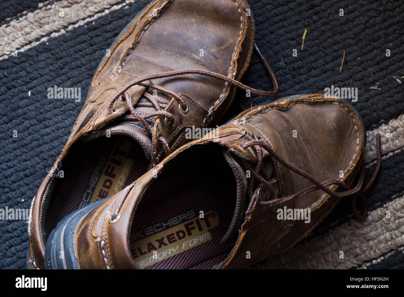 7d74301f Un par de zapatos rotos en cubierta sentada sobre una alfombra de entrada.
