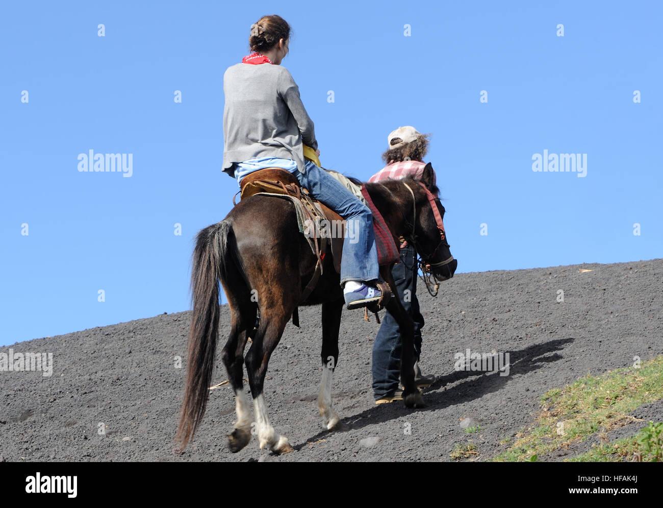 Un turista a caballo es llevado hasta las laderas de lava negra del activo Volcán de Pacaya, Cono Mackenney. Imagen De Stock