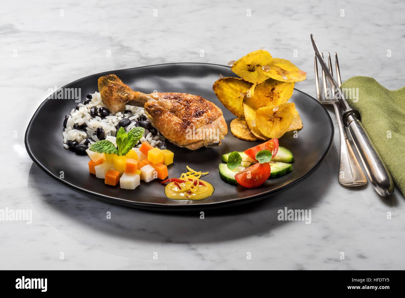 Típica comida cubana, pollo, arroz con frijoles negros, plátanos fritos, patatas fritas, y ensalada de verduras. Foto de stock