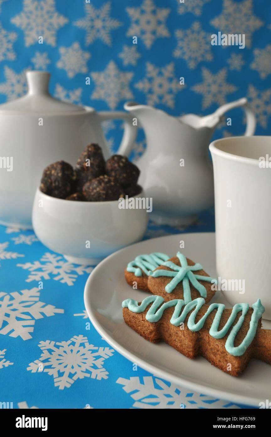 Cerca de diversas fiestas navideñas galletas dulces, golosinas y sobre fondo azul con copos de nieve blanca Imagen De Stock